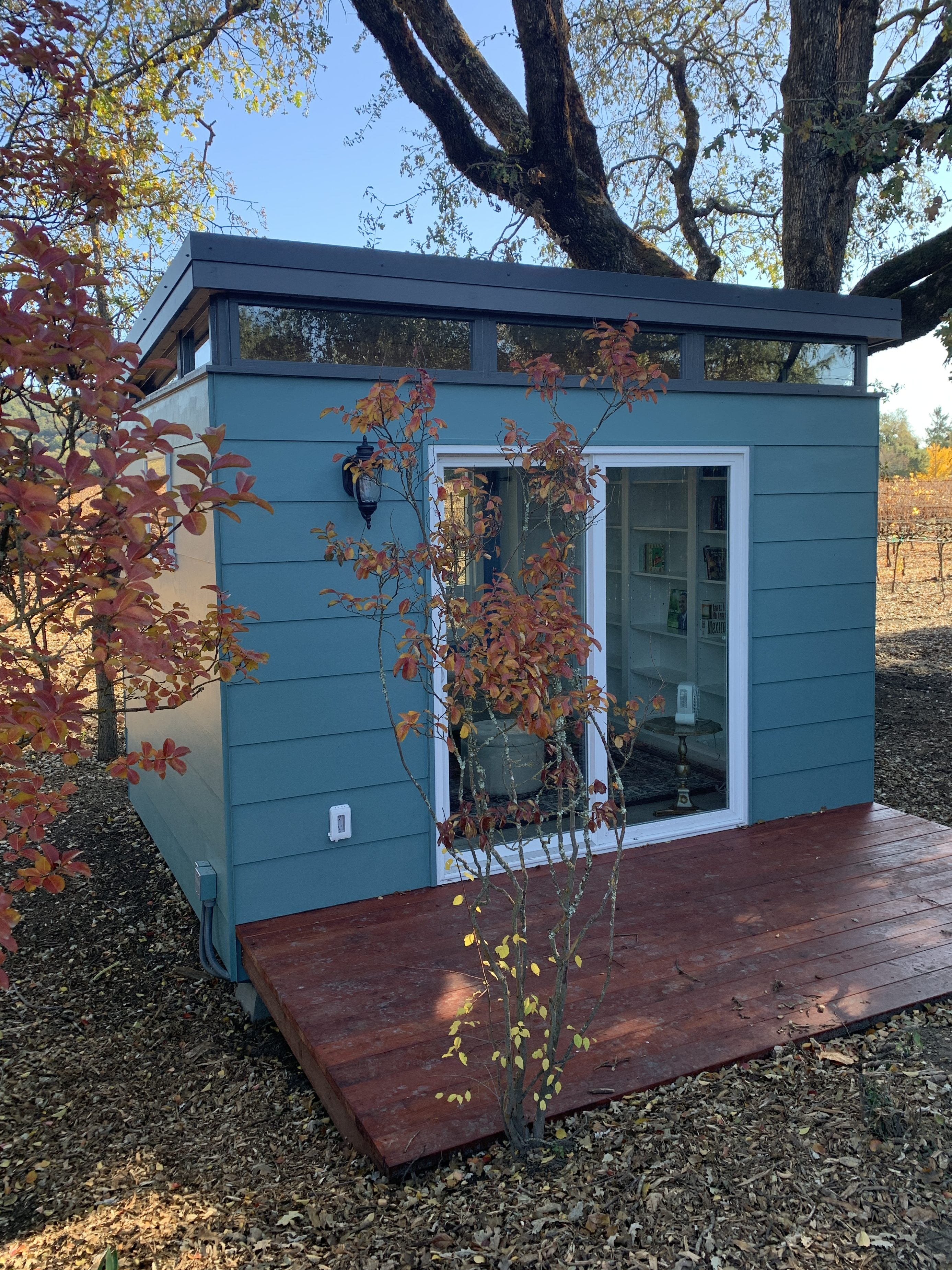 A blue-green shed in fall foliage.